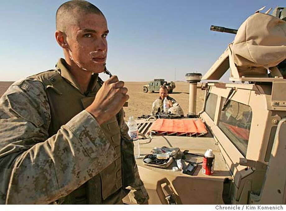 """After driving to a safe area the Marines perform """"hygiene"""" on themselves and their guns. Here private Dale Fellows shaves as Gunnery Sergeant Derrick Link prepares to do the same.  After an all-night mission outside Sada, b  Marines from the 1st Mobile Assault Platoon, Weapons Company, 3rd Battalion, 6th Marine Regiment wake from their desert bivouacs to discover they are being mortared from the nearby town of al Karabilah. They call in for air support and make a foray into town.  San Francisco Chronicle Photo by Kim Komenich  9/30/05 Photo: Kim Komenich"""