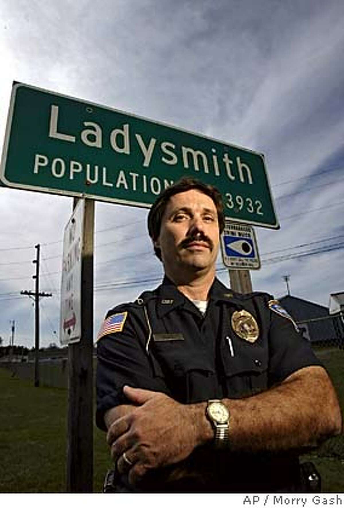 Ladysmith Police Chief Dean Meyer stands near a sign at the edge of town Thursday, April 21, 2005, in Ladysmith, Wis. Meyer has been working on the case involving Robert Rogers for 22 years. Rogers is accused of recruited three of his brothers to do the killing that languished unsolved for 25 years. Two of his brothers sit in jail, accused of murder. A third provided evidence that broke open the case and won't be charged. (AP Photo/Morry Gash)