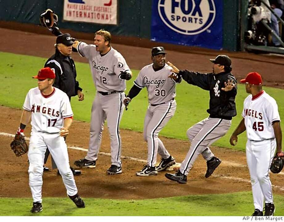 Chicago White Sox's A.J. Pierzynski, (12), Tim Raines, (30) and manager Ozzie Guillen, second from right, run out to argue with the umpire after the Los Angeles Angels pitcher Kelvim Escobar, far right, missed Pierzynski with a tag as he headed to first base in the eighth inning during Game 5 of the American League Championship Series in Anaheim, Calif., Sunday, Oct. 16, 2005. Escobar was given an error after he failed to tag Pierzynski with the ball in his right hand. (AP Photo/Ben Margot) Photo: BEN MARGOT