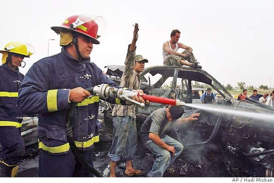 Fire fighters extinguish fire after a suicide car bomber crashed into an Iraqi police checkpoint killing 33 and injuring 75 at an entrance to Sadr City, the capital's biggest Shiite Muslim neighborhood, in Baghdad, Iraq, Wednesday, April 18, 2007. Four large bombs exploded in mostly Shiite areas across Baghdad on Wednesday, killing at least 157 people and wounding scores as violence climbed toward levels seen before the U.S.-Iraqi campaign to pacify the capital began two months ago. (AP Photo/Hadi Mizban) Photo: HADI MIZBAN