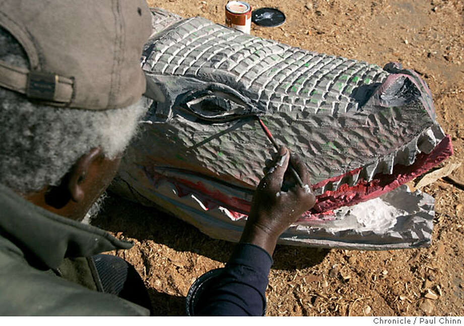 Artist John Abduljaami applies a coat of paint to add realism. Abduljaami transformed an old tree trunk into a crocodile at his studio in Oakland, Calif. on Thursday, March 22, 2007. It takes roughly three days for Abduljaami to turn a log into a work of art. Several of his pieces are currently on exhibit at the Arts Benicia gallery thru April 22.  PAUL CHINN/The Chronicle  **John Abduljaami Photo: PAUL CHINN