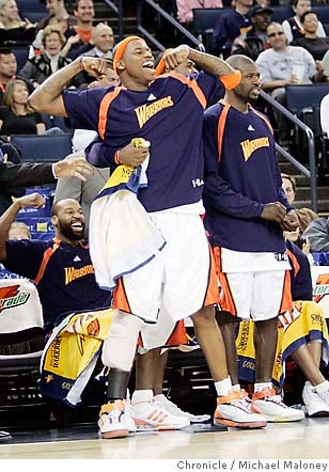 Al Harrington (center) and Baron Davis flex their muscles in the closing minutes of the win over Minnesota. Chronicle photo by Michael Maloney