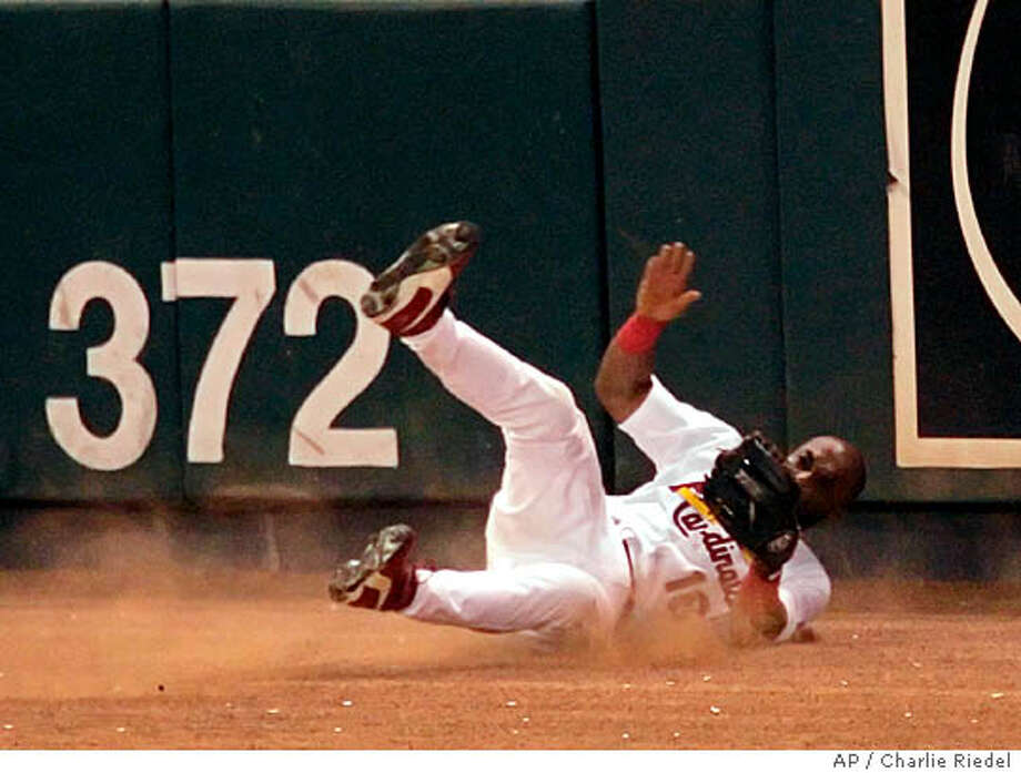 St. Louis Cardinals left fielder Reggie Sanders (16) crashes on the track after failing to catch a triple by Houston Astros' Adam Everett to drive in Chris Burke in the eighth inning of Game 2 of the National League Championship Series, Thursday, Oct. 13, 2005, in St. Louis. Sanders left the game with a low back sprain. (AP Photo/Charlie Riedel) Ran on: 10-15-2005  Reggie Sanders rolls on the ground after hitting the wall in Game 2. Ran on: 10-15-2005  Reggie Sanders rolls on the ground after his painful fall in Game 2. Photo: CHARLIE RIEDEL
