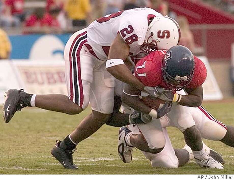 Arizona's Mike Bell (11) is tackled by Stanford's Peter Griffin (28) and Babatunde Oshinowo, in back, during the second quarter Saturday, Oct. 15, 2005, in Tucson, Ariz. (AP Photo/John Miller) Photo: JOHN MILLER