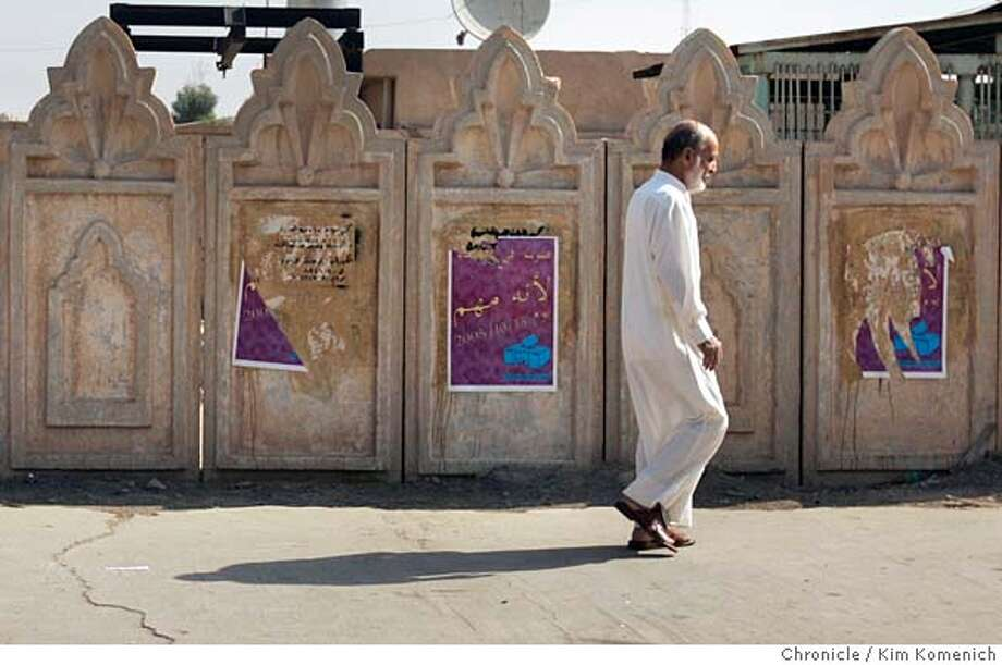 Najim Abdullah walks past get-out-the-vote posters on his way to the polls  We tour the Tikrit area as the Iraqi consititutional referendum takes place. Our story features two aspects of the referendum: the vote itself, at some of the 33 Tikrit area polling places, and then the backstory- the role of Lt. Col. Todd Wood and soldiers from the 2nd Battalion, 7th Infantry Regiment,1st Brigade of the Third Infantry Division, U.S. Army in making sure the Iraqi Army and Police are ready to support safe and secure elections without direct U.S. help.  San Francisco Chronicle Photo by Kim Komenich  10/15/05 Photo: Kim Komenich