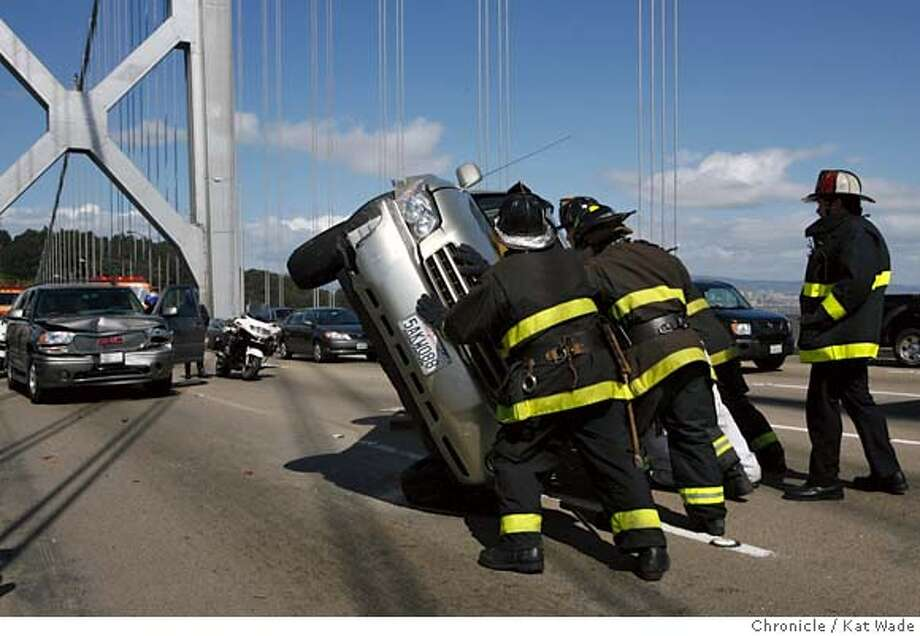 BRIDGEaccident_0074_KW.JPG  STANDALONE: San Francisco firefighters upright a car involved in a three car accident on the West bound top span of the Bay Bridge just West of Treasure Island at the beginning of the afternoon commute on April 17, 2007. The accident that happened at 2:58 p.m. closed lanes 4 and 5 until 3:36 p.m. Acoording to the CHP who also said there was one minor injury. Kat Wade/The Chronicle Reuben Jacobson , Erin Williams and D. Fuselier (CQ, Subject) Mandatory Credit for San Francisco Chronicle and photographer, Kat Wade, No Sales Mags out Photo: Kat Wade
