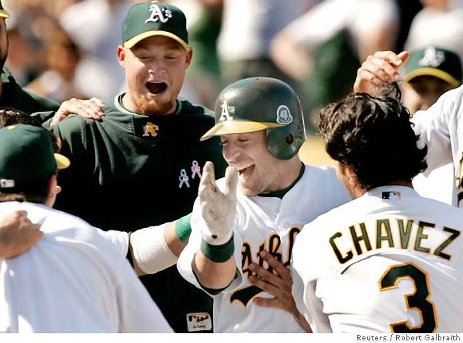 Oakland Athletics Marco Scutaro (C) leaps into the arms of awaiting teammates after hitting a three-run, walk-off home run in the ninth inning against the New York Yankees during their MLB American League baseball game in Oakland, California April 15, 2007. REUTERS/Robert Galbraith (UNITED STATES) 0 Photo: ROBERT GALBRAITH