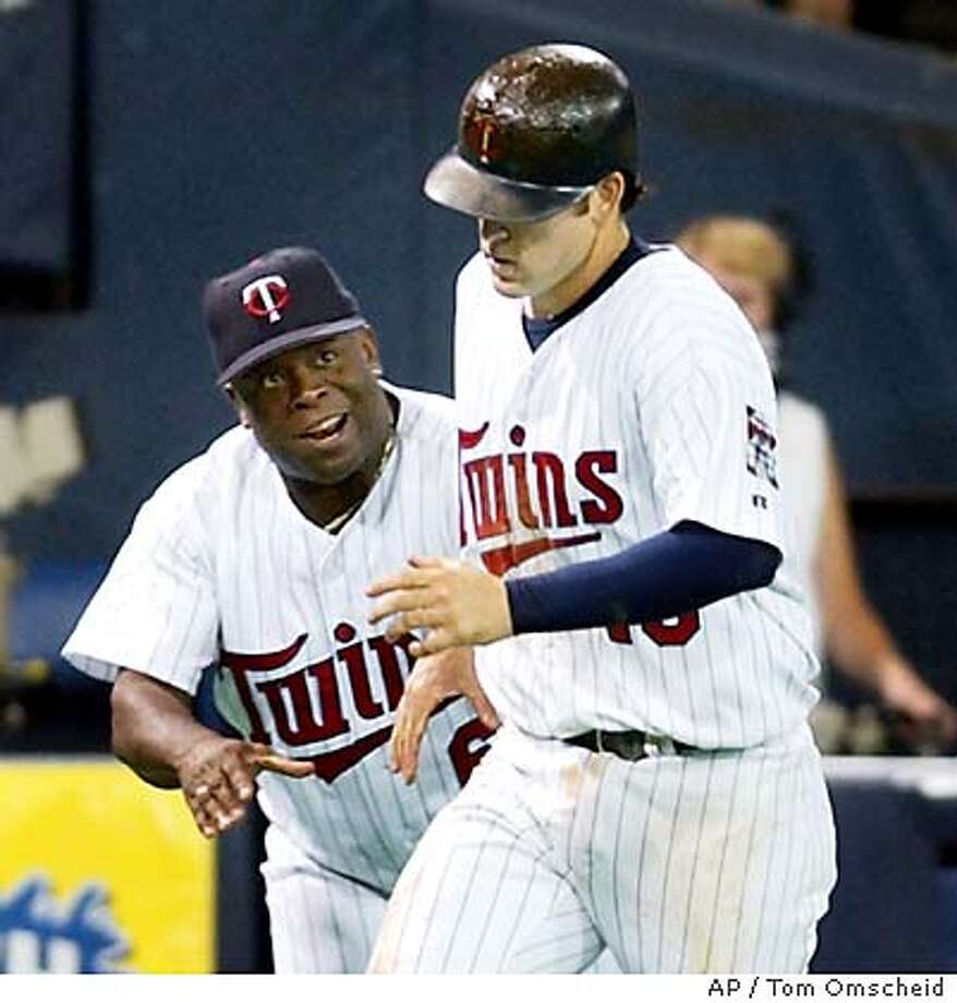 Minnesota Twins third base coach Al Newman, left, congratulates Doug Mientkiewicz, right, as Mientkiewicz heads for home after hitting a two-run home run off Oakland Athletics pitcher Mark Mulder during the fifth inning Saturday, July 19, 2003, in Minneapolis. (AP Photo/Tom Omscheid) Photo: TOM OLMSCHEID