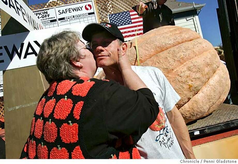 "PUMPKIN11_0062_PG.JPG Mary Lou Holland wife of Joel Holland, gives her husband a big kiss. They just won for the pumpkin that weighed the most at 1229 lbs circumfrance is 12 feet 10 inch. They are from Puyallup Washington the annual pumpkin weighing in half moon bay is officially called the SAFEWAY WORLD CHAMPIONSHIP PUMKIN WEIGH-OFF. the winner will receive $5/lbs; there's a special prize of $500 for the ""most beautiful pumpkin.""  San Francisco Chronicle, Penni Gladstone  Photo taken on 10/10/05, in Half Moon Bay, Photo: Penni Gladstone"