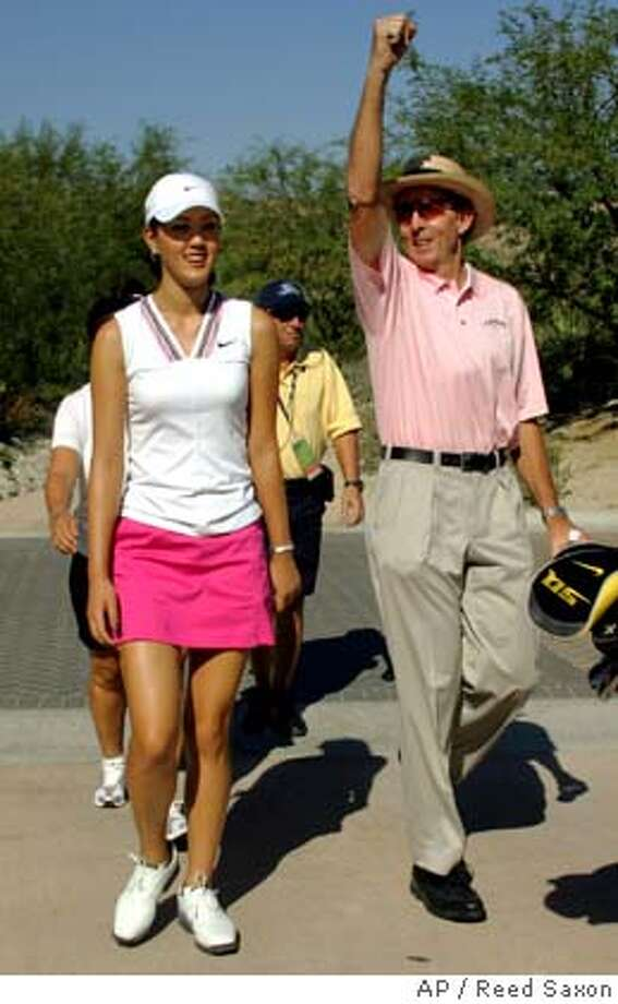 Michelle Wie and her instructor David Leadbetter share a moment as they walk the course as she plays in the Pro-Am round of the Samsung Challenge at Bighorn Golf Club in Palm Desert, Calif., Wednesday, Oct. 12, 2005. Wie is playing in her first professional tournament after turning pro on her 16th birthday Tuesday, Oct. 11. (AP Photo/Reed Saxon) Photo: REED SAXON