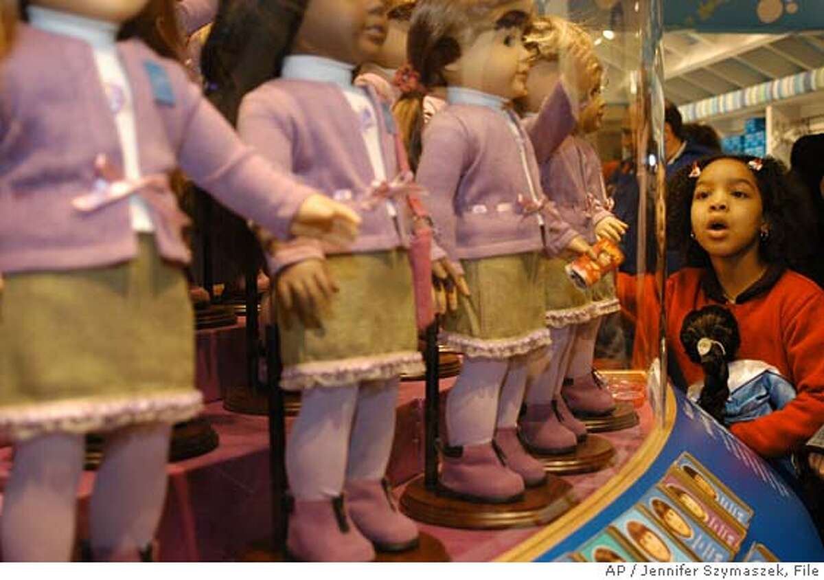 ** FILE ** Samantha Small, 7, of Brooklyn, looks at dolls for sale at the American Girl Place store in New York, in a Saturday, Nov. 8, 2003 file photo. American Girl, manufacturer of a popular line of dolls and children's books, has become a target of conservative lobbying groups threatening a boycott unless the toymaker cuts off contributions to a youth organization that supports abortion rights and gay rights. (AP Photo/Jennifer Szymaszek, File) NOV. 8, 2003 FILE PHOTO