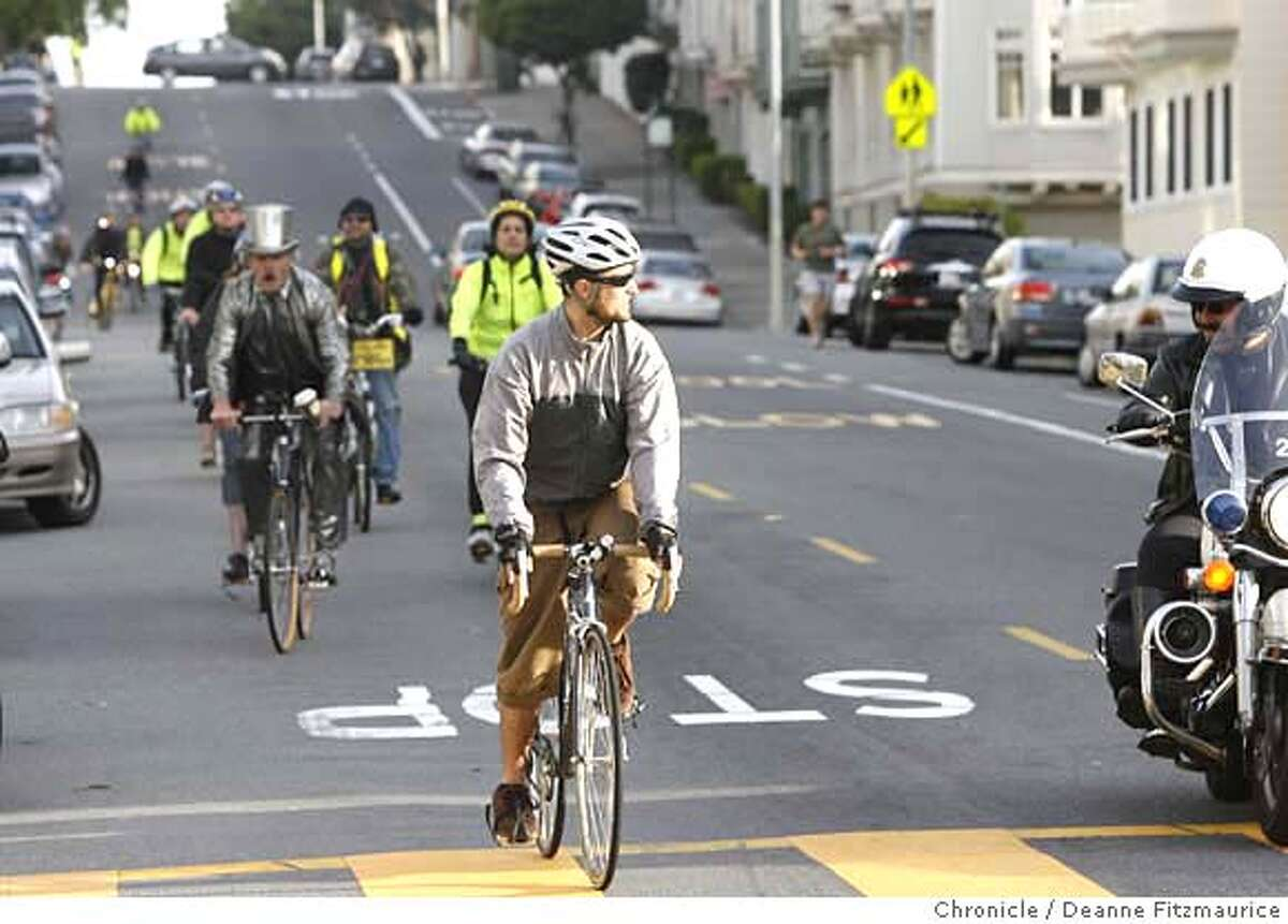 A police office who accompanied the ride, watches a a rider stops at a sign sign. Bike riders take part in Critical Manners, a polite alternative to Critical Mass bike ride in San Francisco on 4/13/07. Deanne Fitzmaurice / The Chronicle