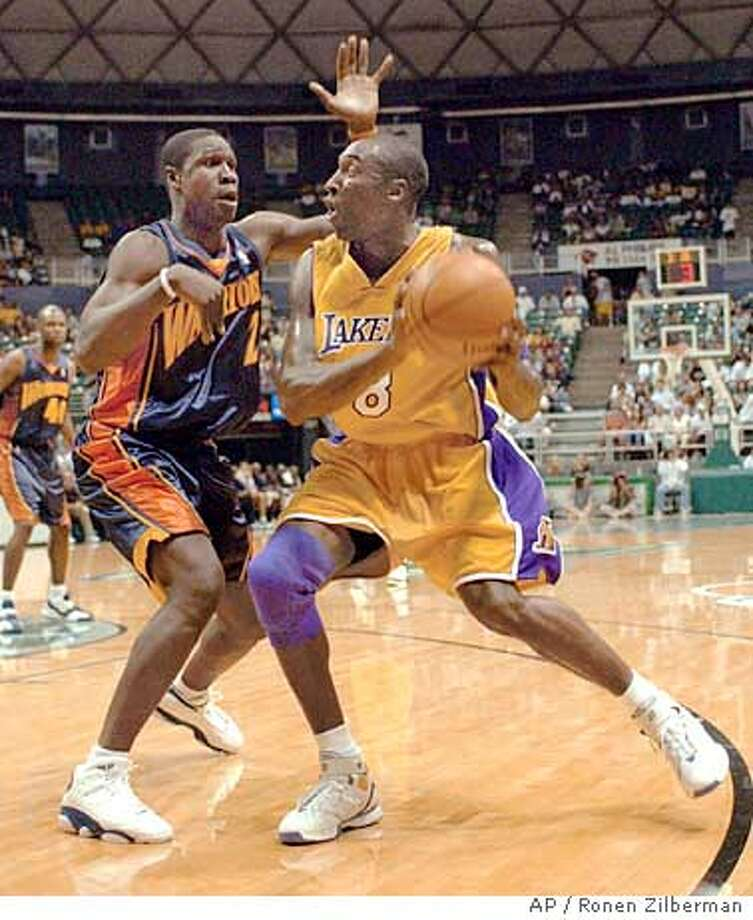 Los Angeles Laker's Kobe Bryant, right, goes to the basket against Golden State Warrior's Mickael Pietrus during a preseason game in Honolulu, Hawaii, Tuesday, Oct. 11, 2005. (AP Photo/Ronen Zilberman) Photo: RONEN ZILBERMAN