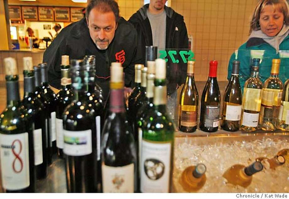 BASEWINE13_028_KW.JPG  (L to R) Antonio Rinaldi checks out the available labels at the California Wine Bar while his son Daniel Rinaldi, 16, watches and Corby Hughes from Minden, Nevada choose a Clos du Bois at AT&T Park on Wednesday April 4, 2007 when the San Francisco Giants lost to the the San Diego Padres on Opening Night at AT&T Park in San Francisco. Kat Wade/The Chronicle Mandatory Credit for San Francisco Chronicle and photographer, Kat Wade, No Sales Mags out Photo: Kat Wade