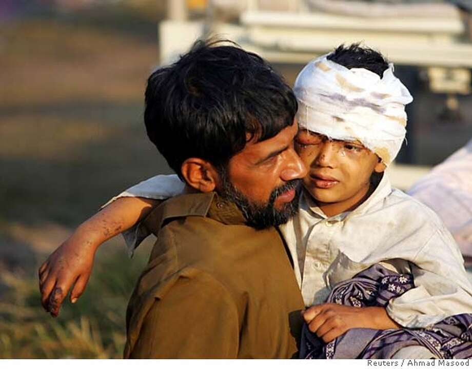 An injured Kashmiri child sits on his fathers lap as they wait to be sent to a hospital by helicopter in Muzaffarabad, capital of Pakistan-controlled Kashmir, October 10, 2005. Rescuers dug through the night on Monday in the hope of finding more survivors of the Pakistan earthquake, after it killed more than 20,000 people and buried hundreds alive in rubble. REUTERS/Ahmad Masood [Photo via NewsCom] 0 Photo: AHMAD MASOOD