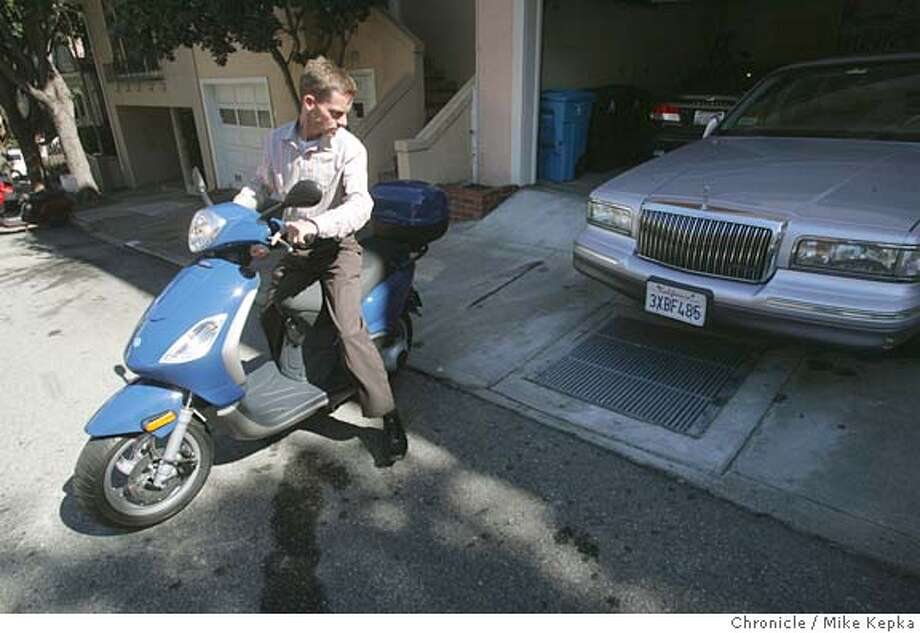 Ultan MacGabhann is trading his Lincoln town car for a 90 mile per gallon scooter. He now uses it to commute the 10 blocks to his work in San Francisco. 9/28/05 Mike Kepka / The Chronicle Photo: Mike Kepka