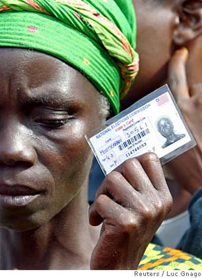 A woman holds her voter's card for the presidential and parliamentary elections in Monrovia October 11, 2005. Liberians crowded polling stations on Tuesday to vote in the West African nation's first elections since a brutal civil war that ended two years ago. Out of 22 presidential hopefuls, former AC Milan striker and millionaire soccer star Weah, 39, and 66-year-old former World Bank economist Ellen Johnson-Sirleaf are seen as the frontrunners. REUTERS/Luc Gnago Photo: LUC GNAGO