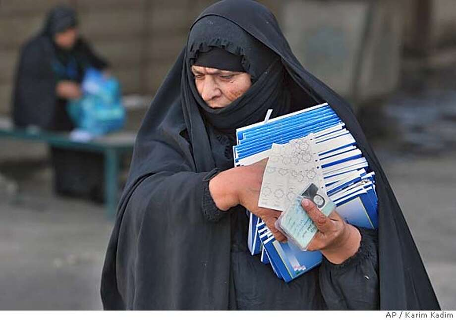 An Iraqi food distribution agent carries new constitution copies in Baghdad, Iraq, Monday, Oct. 10 2005. Copies of the draft constitution are sent to Iraqis together with their food rations.Insurgents launched a new salvo of attacks five days ahead of the country's crucial constitutional referendum, killing at least 12 Iraqis and a U.S. soldier with suicide car bombs, roadside bombs and drive-by shootings on Monday, police said.(AP Photo/Karim Kadim) Photo: KARIM KADIM