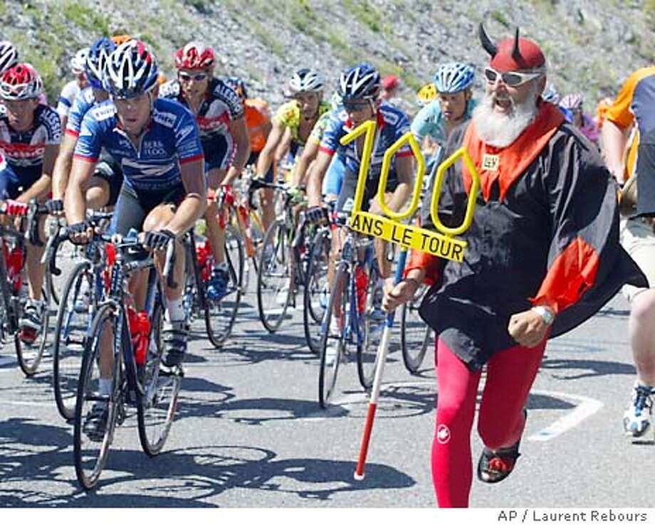 Cycling supporter dressed as the devil, Didi Senft, from Kolpin, Germany, right, cheers Lance Armstrong, of Austin, Texas, left, during the ascent of the Col du Galibier pass during the 8th stage of the cycling race, Sunday, July 13, 2003, between Sallanches and L'Alpe d'Huez, French Alps. The inscription on Senft's stick reads : One hundred years, the Tour. (AP Photo/Laurent Rebours) Photo: LAURENT REBOURS