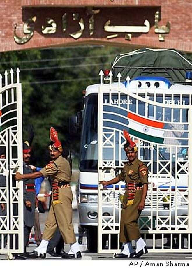 Indian Border Security Force soldiers open the gates for the Lahore-Delhi bus to enter India at Wagah, Friday, July 11, 2003. The bus service between the India and Pakistan resumed Friday after it was disrupted 18 months ago by threats of war between the hostile, nuclear-armed neighbors. (AP Photo/Aman Sharma) Photo: AMAN SHARMA