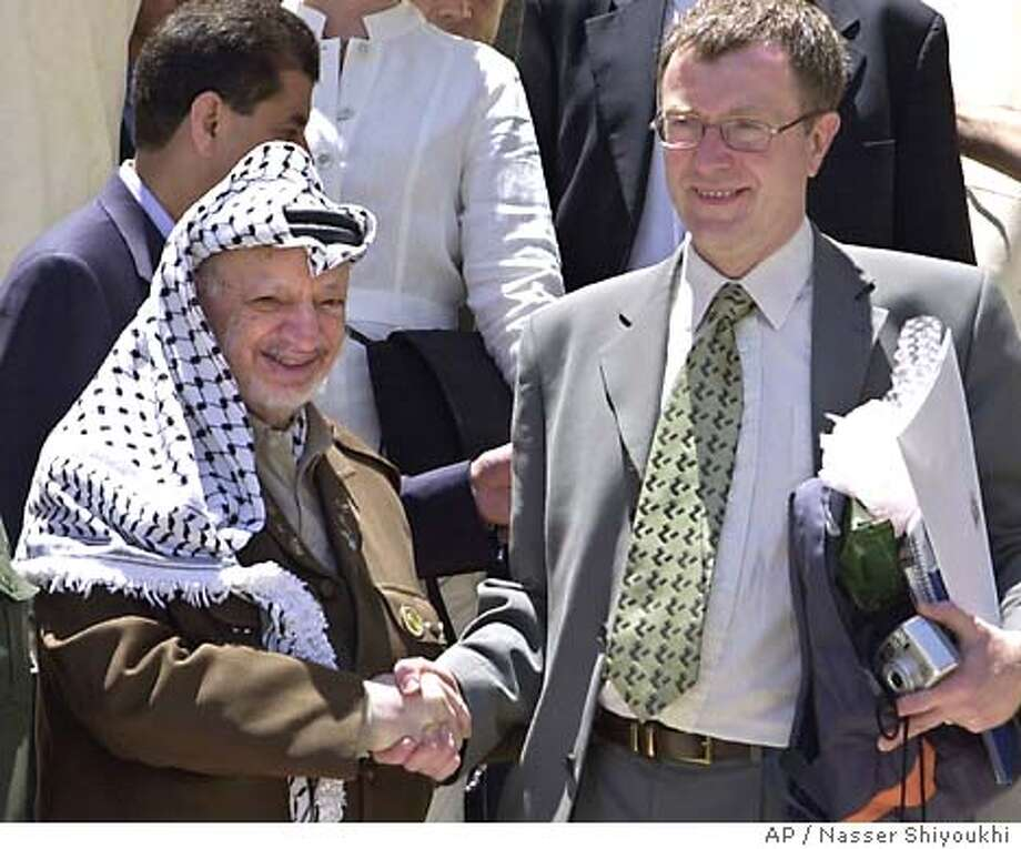 Palestinian leader Yasser Arafat shakes hands with British MP Richard Brown at the entrance of his office in the West Bank town of Ramallah after a meeting with a delegation of the British parliament Saturday, July 12, 2003. As he prepares to travel to London, Israel's Prime Minister Ariel Sharon said in a newspaper interview published Saturday that European leaders were undermining a fledgling peace effort by continuing to meet and maintain ties with Yasser Arafat. (AP Photo/Nasser Shiyoukhi) Photo: NASSER SHIYOUKHI