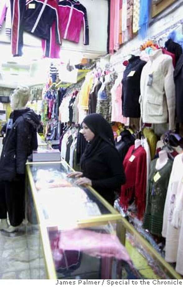 A saleswomen behind a counter inside Al-Masara, a discount clothing store in Baghdad, Iraq, on Feb. 22, 2007.  Today, the majority of women here must at the very least cover their head in public simply as a shield against potential physical attacks and verbal abuse from religious and social extremists. As religious ideology strengthens its grip on Baghdad many women here are increasingly compelled to maintain a balance between their desires to wear modern fashion with the need to submit to traditional Islamic dress codes. PHOTO BY JAMES PALMER/SPECIAL TO THE CHRONICLE Photo: JAMES PALMER/SPECIAL TO THE CHRO