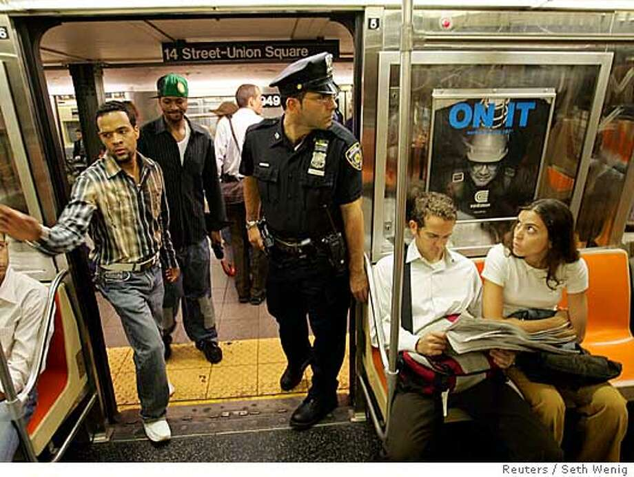 A police officer glances around a subway car in New York City October 7, 2005. Part of the section of New York's Pennsylvania Station where Amtrak trains operate was sealed off on Friday morning because of what authorities said was a police situation, a day after officials warned of a possible attack on the system. The precaution came one day after New York officials said they had intelligence that the city's subway system was under a credible and specific threat of possible attack. REUTERS/Seth Wenig Photo: SETH WENIG