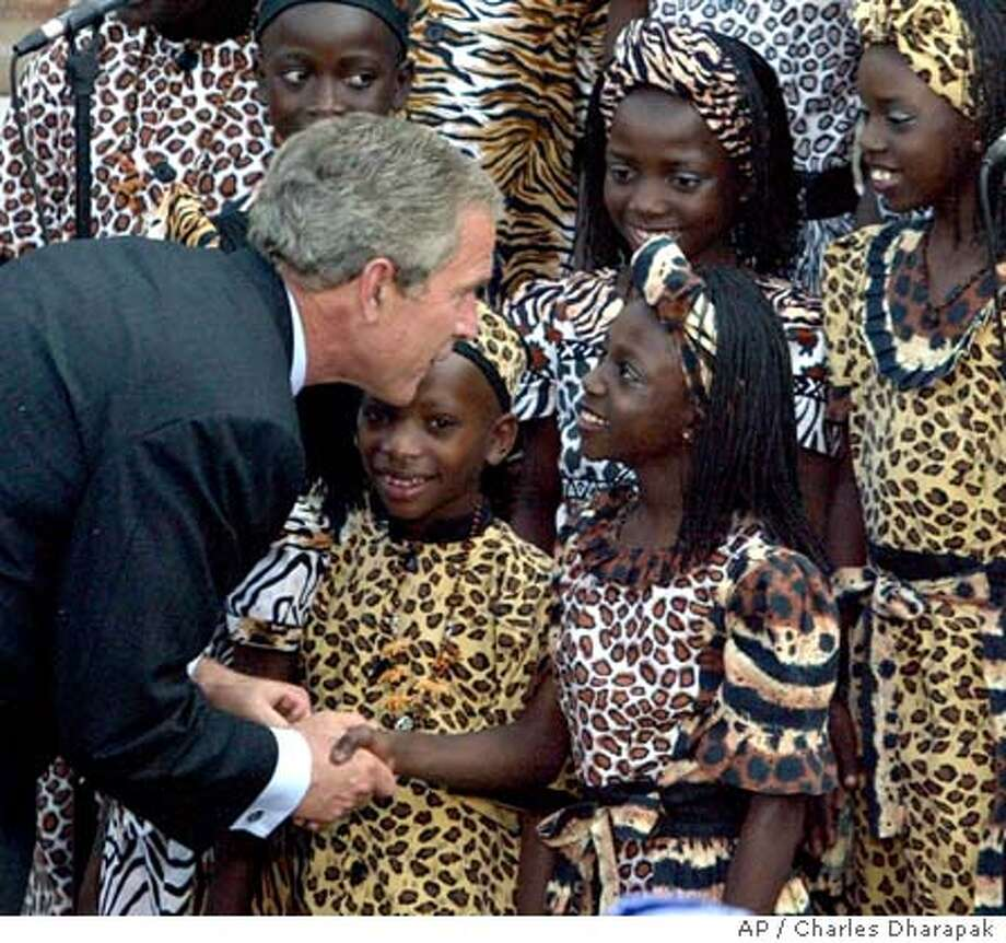 President Bush greets a member of the Ugandan Watoto Children's Choir after they performed for him at the AIDS Support Organization Center (TASO) in Entebbe, Uganda, Friday, July 11, 2003. President Bush wants Uganda's journey out of the dark scourge of AIDS to serve as a model for his $15 billion global initiative to contain the pandemic. (AP Photo/Charles Dharapak) Photo: CHARLES DHARAPAK