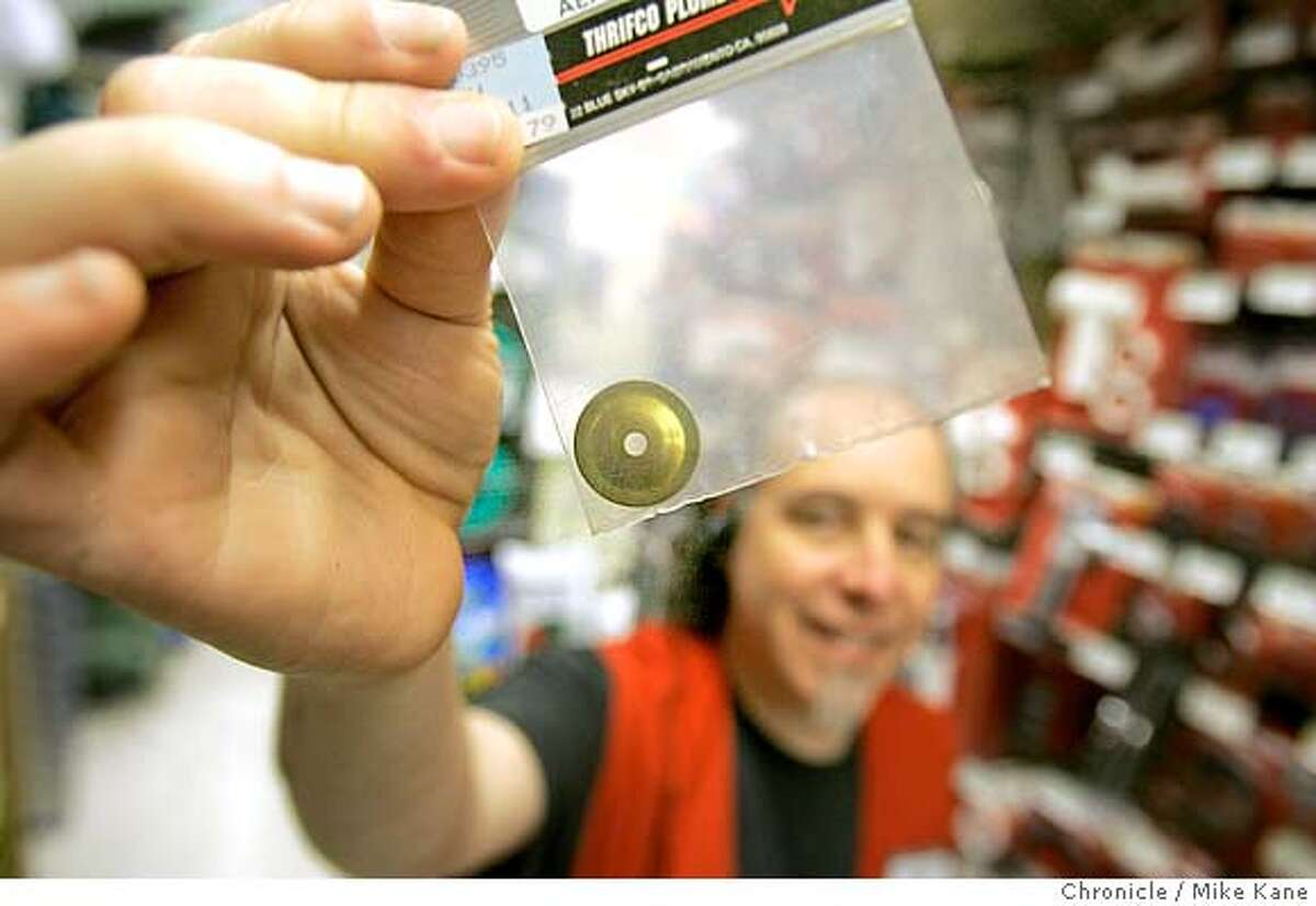 Employee Jon Pogorelskin of Pacifica holds up a flow reduction disk, 79 cents, to be installed in between a shower's aerator and faucet, at Cole Fox Hardware in downtown San Francisco, CA, on Wednesday, April, 11, 2007. photo taken: 4/6/07 Mike Kane / The Chronicle *jon Pogorelskin