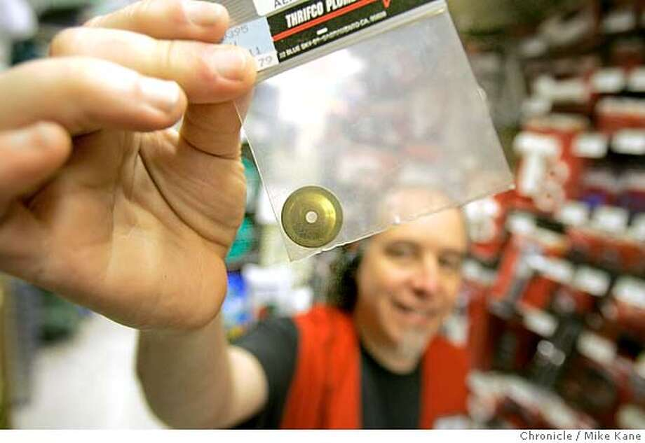 Employee Jon Pogorelskin of Pacifica holds up a flow reduction disk, 79 cents, to be installed in between a shower's aerator and faucet, at Cole Fox Hardware in downtown San Francisco, CA, on Wednesday, April, 11, 2007. photo taken: 4/6/07  Mike Kane / The Chronicle *jon Pogorelskin Photo: MIKE KANE