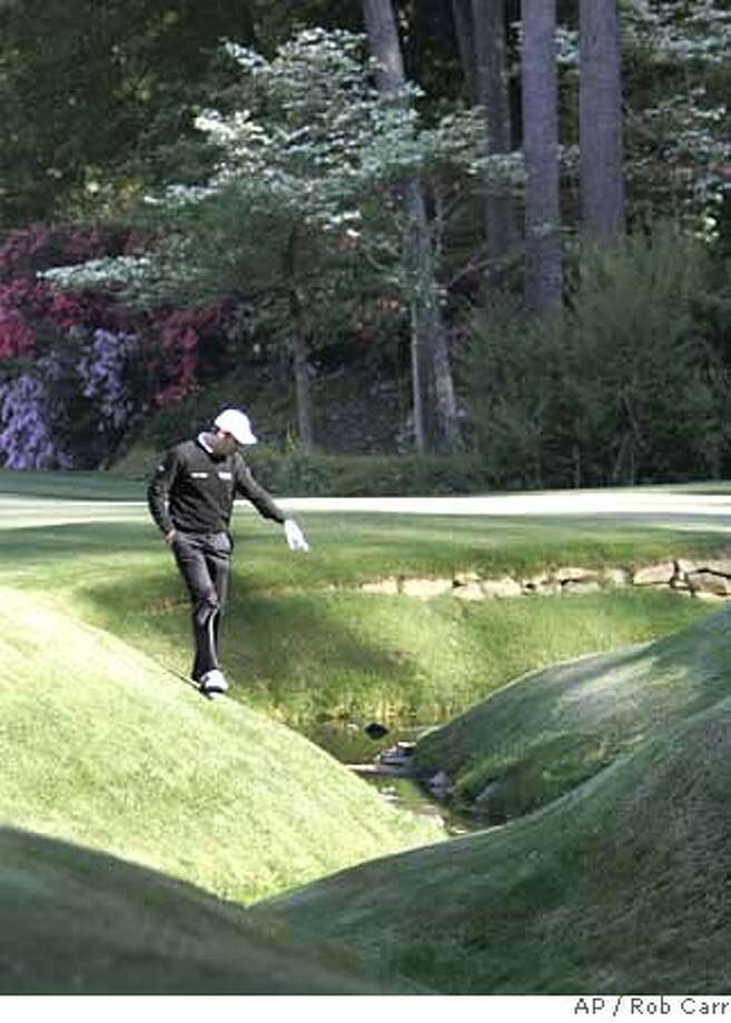 Bradley Dredge, from Wales, looks for his ball in Rae's Creek on the 13th hole during the third round of the 2007 Masters golf tournament at the Augusta National Golf Club in Augusta, Ga., Saturday, April 7, 2007. (AP Photo/Rob Carr) EFE OUT Photo: Rob Carr