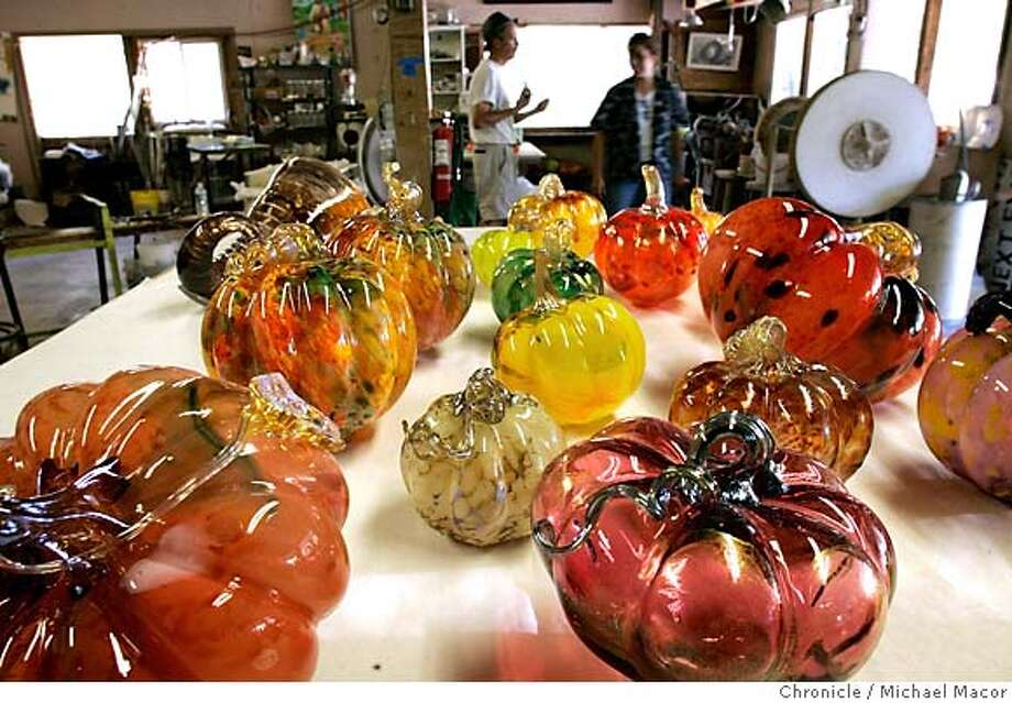 Stanton and Erickson take a break in the background. The glass pumpkins of all shapes and sizes, fill the workshop. Parent Tom Stanton along with other glass-blowing artists, are creating hundreds of glass pumpkins for a fundraiser for Los Altos High School. Last year a similar sale raised $15,000 which went to pay for books, school supplies and art materials. Stanton hopes to someday raise enough money to start a glass-blowing class at the school. 9/22/05 Los Gatos, Ca Michael Macor / San Francisco Chronicle Photo: Michael Macor