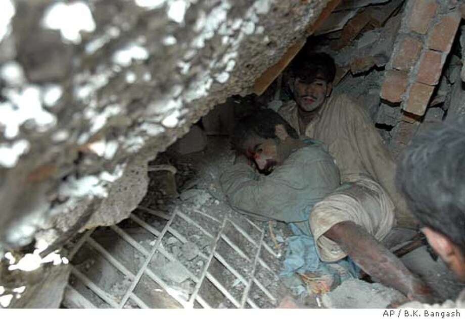 Residents are seen trapped after a housing complex collapsed by a severe earthquake that jolted Islamabad, Pakistan, Saturday, Oct. 8, 2005. A magnitude 7.6 earthquake rocked parts of India, Pakistan and Afghanistan, injuring at least a dozen people and damaging dozens of homes and shops. (AP Photo/B.K.Bangash) Photo: B.K.BANGASH