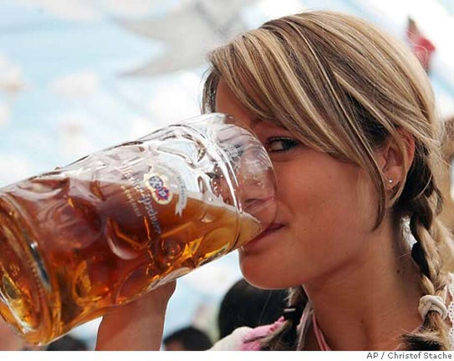 Andrea Wilch drinks a beer during her visit in a marquee of the Oktoberfest in Munich, southern Germany, on Wednesday, Sept. 21, 2005. The Oktoberfest take place until Oct. 3, 2005 and many thousands of visitors will be expected here. (AP Photo/Christof Stache) Photo: CHRISTOF STACHE