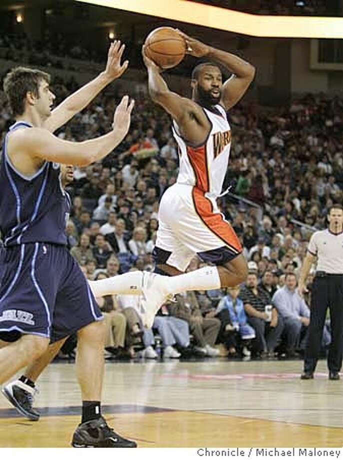 Warriors Baron Davis (5) looks for someone to pass to. At left is Utah Jazz Mehmet Okur (13)  The Golden State Warriors host the Utah Jazz at Oracle Arena in Oakland, CA on Monday night, April 9, 2007.  Photo by Michael Maloney / San Francisco Chronicle ***(Roster) Mehmet Okur, Baron Davis Photo: Michael Maloney