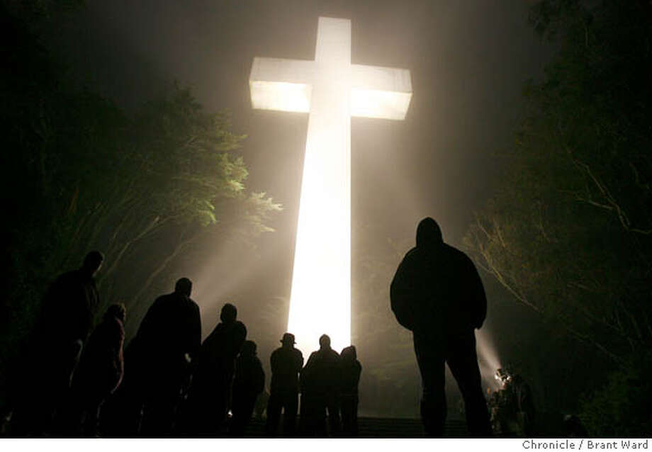 Even before sunrise, the faithful gathered, as dozens of lights lit the cross and the fog rolled over the mountain.  The 85th annual sunrise service at Mt. Davidson Cross was held Sunday morning in the fog and wind. Several hundred gathered under the huge cross for the annual Easter service.  {Brant Ward/San Francisco Chronicle}4/7/07 Photo: Brant Ward
