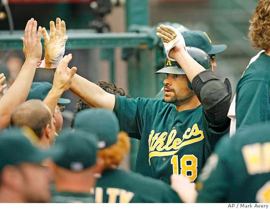 Oakland Athletics catcher Jason Kendall high-fives teammates in the dugout after scoring against the Los Angeles Angels on a Shannon Stewart double in the third inning of a baseball game in Anaheim, Calif., Sunday, April 8, 2007. (AP Photo/Mark Avery) Photo: Mark Avery