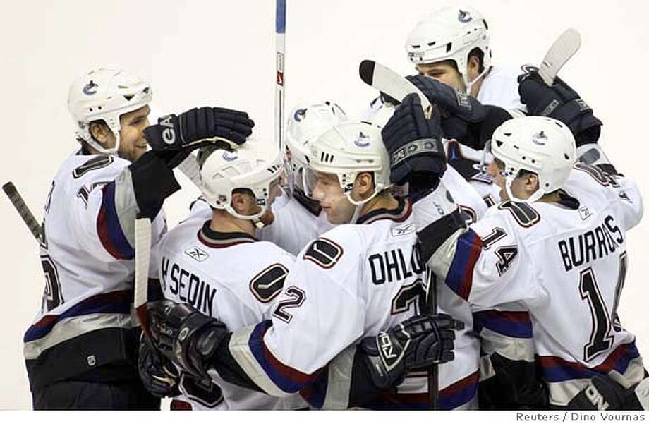 Vancouver Canucks' Mattias Ohlund (2) is mobbed by his teammates after his overtime goal beat the San Jose Sharks' 4-3 during their NHL hockey game in San Jose, California, April 7, 2007. REUTERS/Dino Vournas (UNITED STATES) Photo: DINO VOURNAS