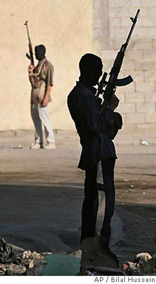 ** RETRAJNSMSSION FOR ALTERNATE CROP ** Suspected insurgents hold weapons in the streets of Ramadi, Iraq, Monday Oct. 3, 2005, following reported clashes between gunmen and Iraqi security forces in the early morning hours. Two Iraqi army trucks were destroyed but there were no reports of casualties. (AP Photo/Bilal Hussein) Photo: BILAL HUSSEIN