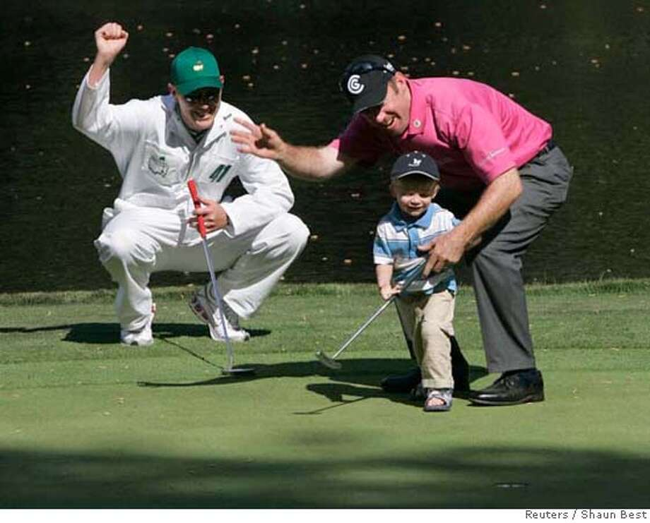 Rod Pampling of Australia (R) reacts after helping his son sink a putt during the annual par-three tournament before the 2007 Masters golf tournament as his caddie Simon Corbett (L) looks on at the Augusta National Golf Club in Augusta, Georgia, April 4, 2007. Play in the Masters tournament begins on April 5. REUTERS/Shaun Best (UNITED STATES) 0 Photo: SHAUN BEST