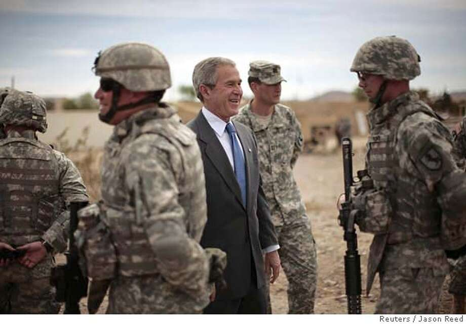 U.S. President George W. Bush laughs among soldiers during his visit to the National Training Center at Fort Irwin in the Californian desert, April 4, 2007. REUTERS/Jason Reed (UNITED STATES) Photo: JASON REED