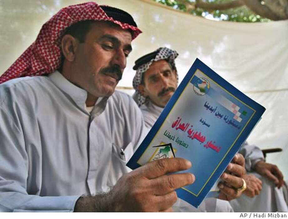 Iraqis read a draft of the country's constitution in Baghdad Wednesday Oct.5 2005. Iraq's National Assembly voted Wednesday to reverse last-minute changes it had made to rules for next week's referendum on a new constitution. The United Nations had criticized the change as unfair to Iraq's Sunni Arab minority, which had threatened to boycott the vote.(AP Photo/Hadi Mizban) Photo: HADI MIZBAN