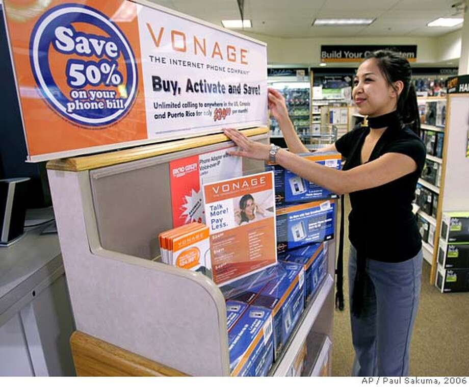 **FILE**Micro Center computer store saleswoman Christine Canasa fixes up a display of Vonage products in Santa Clara, Calif., in this file photo from May 24, 2006.Vonage, the internet phone company, will be barred from signing up new customers as punishment for infringing on patents held by Verizon Communications Inc., under an injunction ordered Friday April 6, 2007. (AP Photo/Paul Sakuma-File) FILE PHOTO FROM MAY 24, 2006 Photo: PAUL SAKUMA