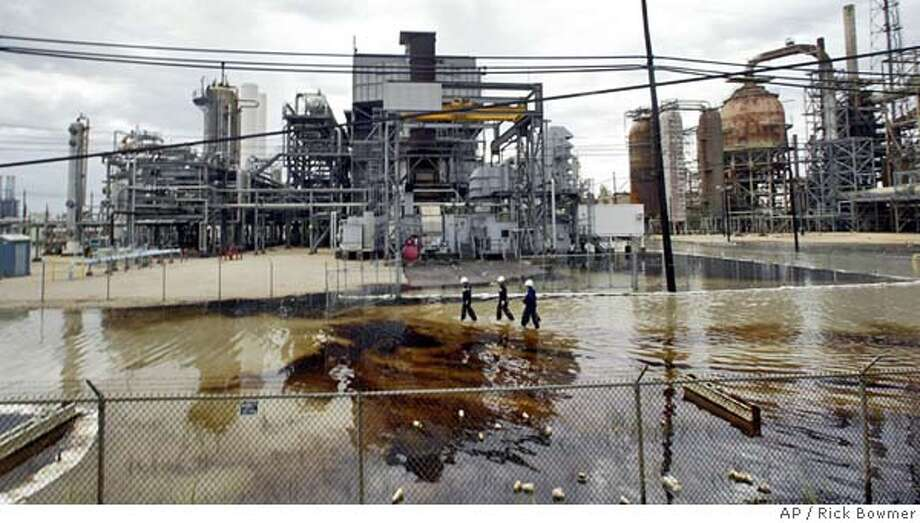 Workers at the Valero's Port Arthur, Texas, refinery inspect an oil spill after it was flooded by Hurricane Rita Saturday, Sept. 24, 2005. Hurricane Rita made landfall along the Texas coast early Saturday morning. (AP Photo/Rick Bowmer) Ran on: 09-27-2005  Inundated refineries are undergoing assessments after Hurricane Rita swamped these facilities in Port Arthur, Texas. Photo: RICK BOWMER