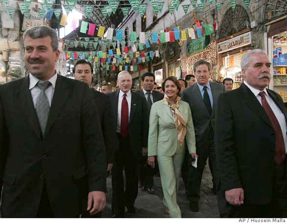 Two Syrian security men, foreground, escorted the U.S. House Speaker Nancy Pelosi, background center, during her tour at a popular market in downtown Damascus, Syria, Tuesday April 3, 2007. President George W. Bush voiced displeasure on Tuesday with House Speaker Nancy Pelosi's trip to Syria, saying it sends mixed signals to the region and to the government of President Bashar Assad. (AP Photo/Hussein Malla) Photo: HUSSEIN MALLA