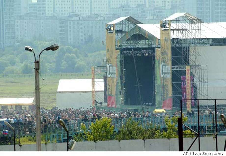 People watch the scene of the bomb blasts at a rock festival at the Tushino airfield in subarban Moscow, Saturday,July 5, 2003. Two women suicide bombers blew themselves up at a giant rock festival in suburban Moscow on Saturday, killing at least 16 people, Russian officials said. (AP Photo/  Ivan Sekretarev) Photo: IVAN SEKRETAREV