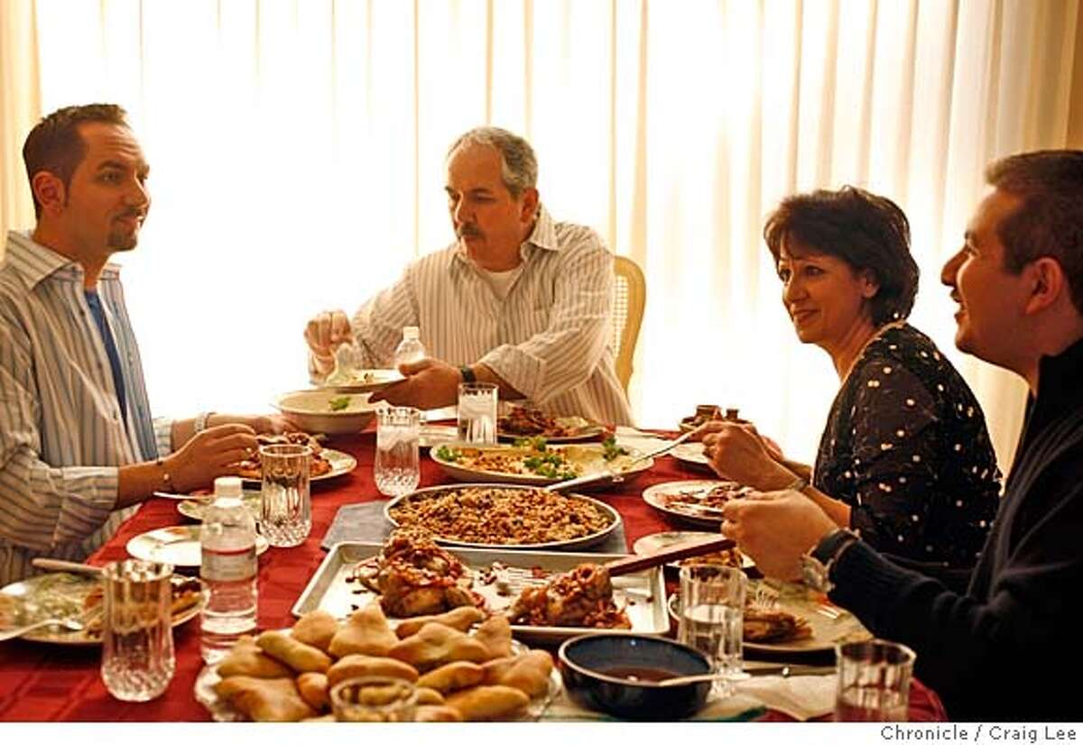 """EASTER04_270_cl.JPG Story on Easter week. This year, Greek Orthodox and Catholic Easter fall on the same date. The family of Samir Nassar, Palestinian Christians, one of whom is Catholic and one Orthodox, will cook some of the traditional easter dishes of both groups. Photo of the Nassar family gatered around the table to eat, left-right: Samer (son), Samir, Georgette """"Juju"""" (Samir's wife), and Suheil """"Soosh"""" (younger son). Event on 3/3/07 in Hercules. photo by Craig Lee / The Chronicle MANDATORY CREDIT FOR PHOTOG AND SF CHRONICLE/NO SALES-MAGS OUT"""