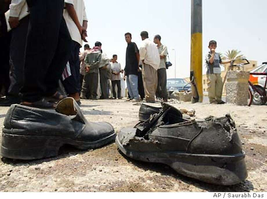 A pair of shoes lies at the scene of an explosion in Ramadi, 95 kilometers (60 miles) west of Baghdad , Iraq, Saturday July 5, 2003. A powerful explosion killed at least seven Iraqi police recruits and injured scores of others as they marched in a graduation ceremony in Ramadi. The blast occurred as the police were marching from a local boys school where they had undergone a five-day U.S. led training course, to a nearby government building, said a survivor. (AP Photo/Saurabh Das) Photo: SAURABH DAS