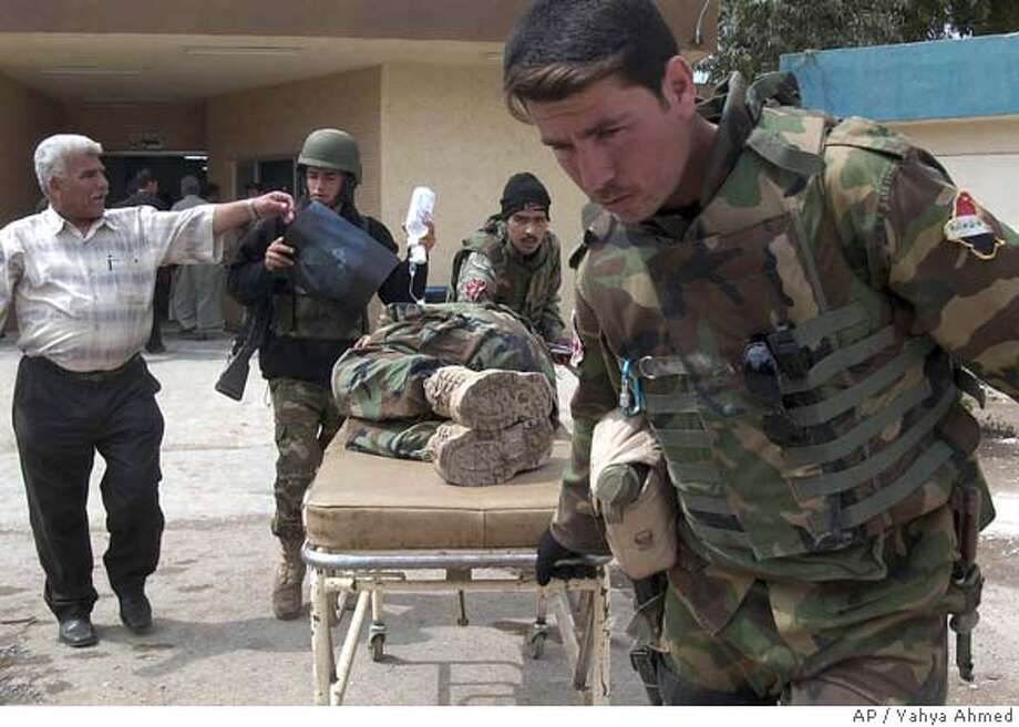 Iraqi soldiers wheel their wounded comrade at a hospital in Kirkuk, Iraq, 290 kilometers (180 miles) north of Baghdad, Tuesday, April 3, 2007. Five soldiers were injured when their patrol was struck by a road side bomb. (AP Photo/Yahya Ahmed) Photo: YAHYA AHMED