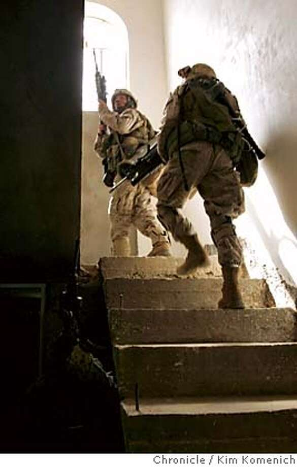 "IRAQ03_BORDER_0175_KK.JPG  Marines charge up the stairs in one of four hones where they belieive a sniper fled after firing at a Marine patrol.  Marines from the Lima Company 3rd Battalion, 6th Marines Regiment, attached to the 2nd Regimental Combat Team in the second day of ""Operation Iron Fist."" they perform house-to-house searches in the town of Sada, on the Iraq Syrian Border. They also blow up the the unexploded parts of a huge bomb composed of several tank and mortar shells that partially detonated earlier in the day causing an Abrams tank to move sideways several feet. San Francisco Chronicle Photo by Kim Komenich  10/2/05 Photo: Kim Komenich"